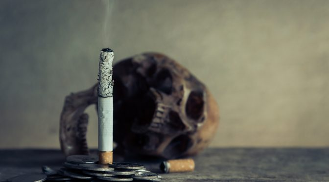 cigarette burning with a skull in the background