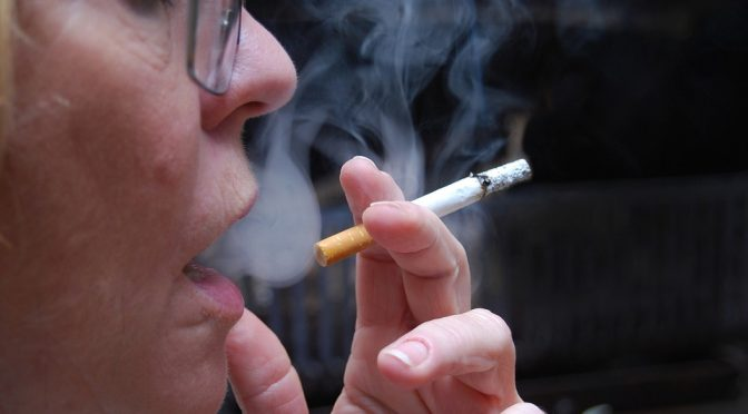 person holding a cigarette and inhaling smoke